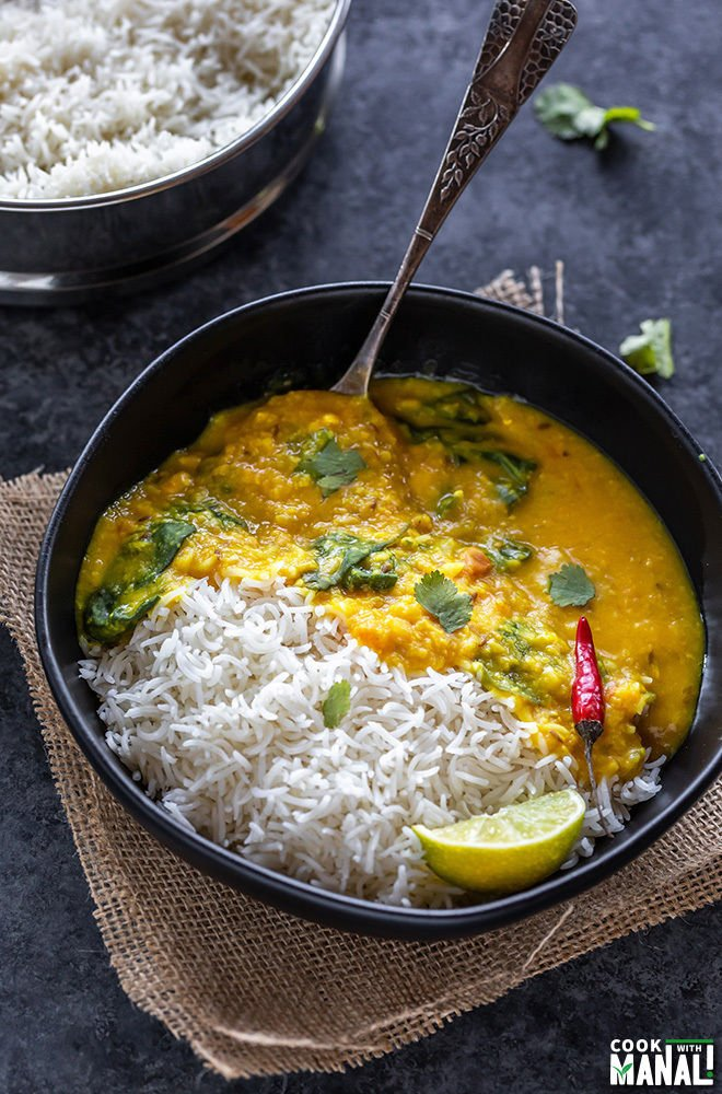 rice and dal in a black bowl with a red chili and a spoon