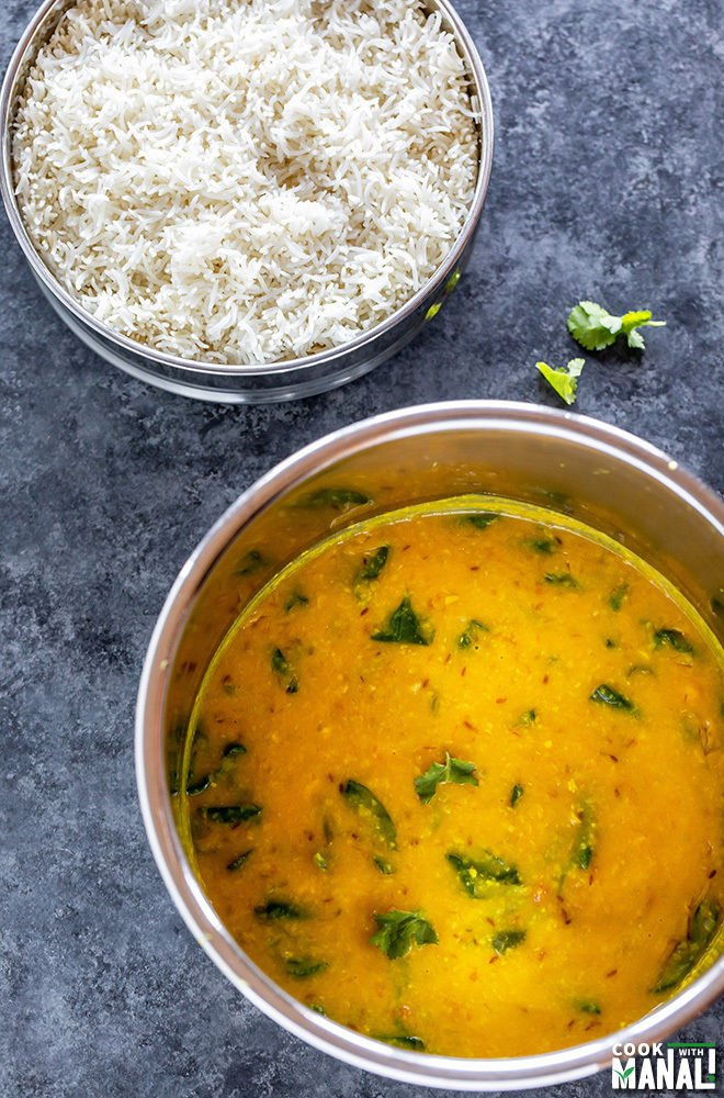 instant pot with cooked dal and a bowl of rice in the back