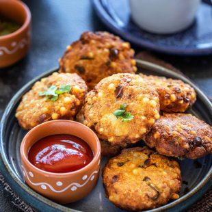 sabudana vada in a plate served with a small bowl of tomato ketchup and a cup of chai in the background