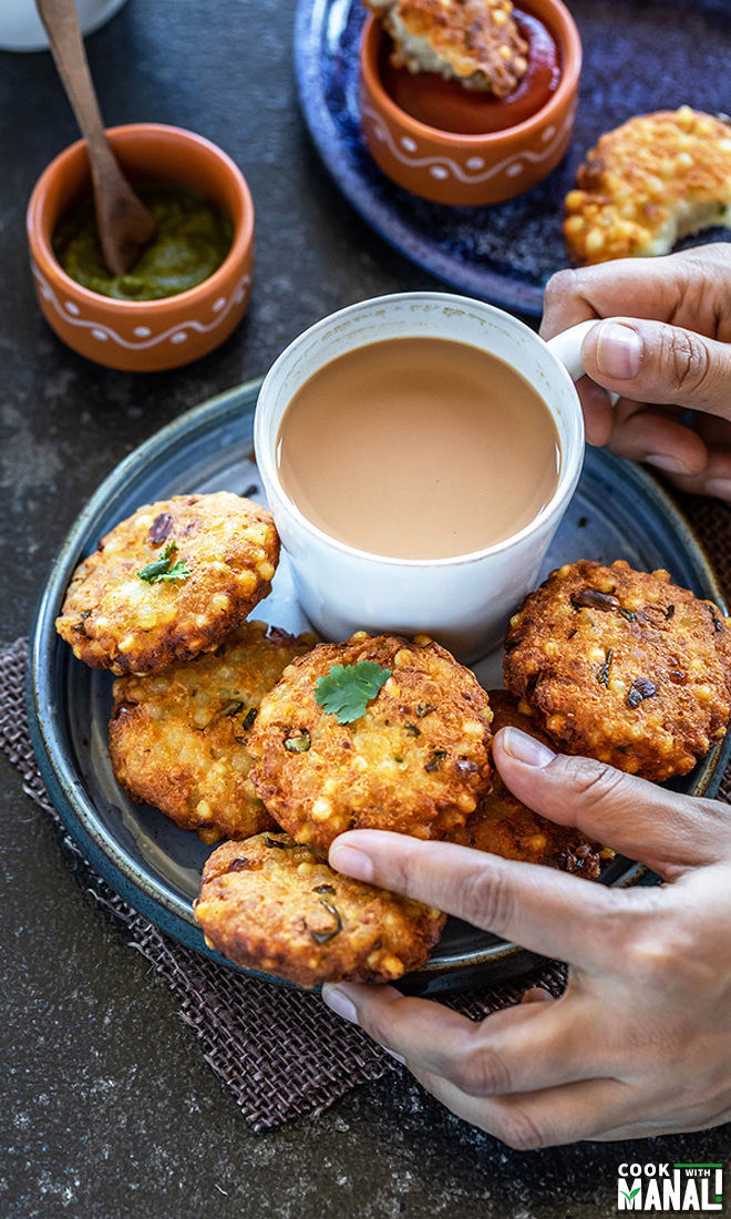 hand holding a sabudana vada and cup of chai