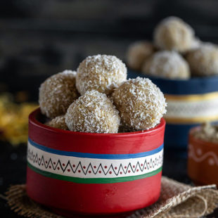 thandai coconut ladoo in a red color bowl with more ladoos and some flowers in the background