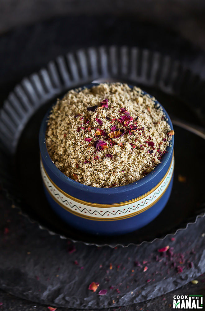 thandai masala powder in a blue bowl sprinkled with dried rose petals on top