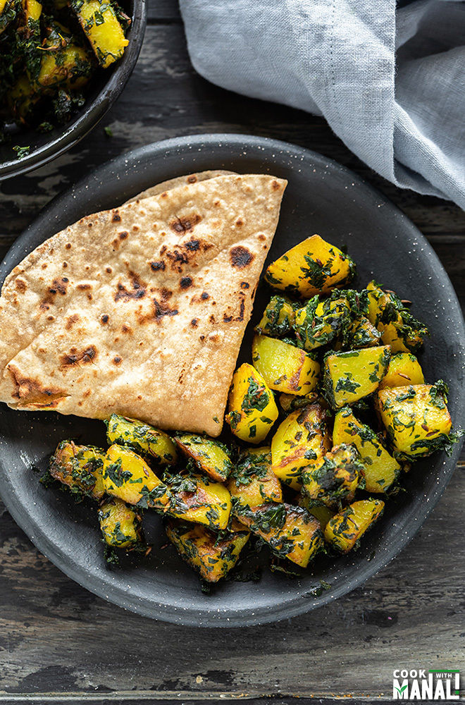 aloo methi served in a black round plate with a roti