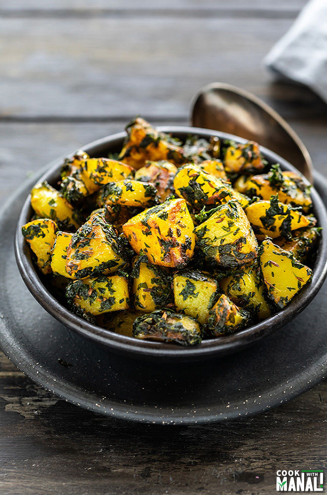 aloo methi in a black bowl with a spoon on the side