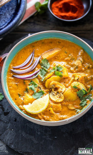 Aloo Mushroom Masala served in a bowl garnished with sliced onions, lemon wedge and cilantro