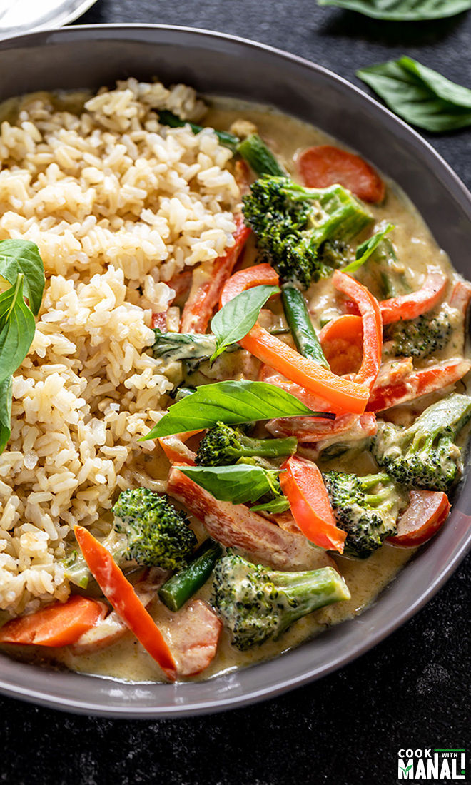 vegan thai green curry served with brown rice in a black bowl