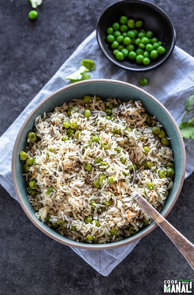 overhead shot of matar pulao in a bowl with a spoon with a small bowl of green peas and cilantro in the background and on the sides