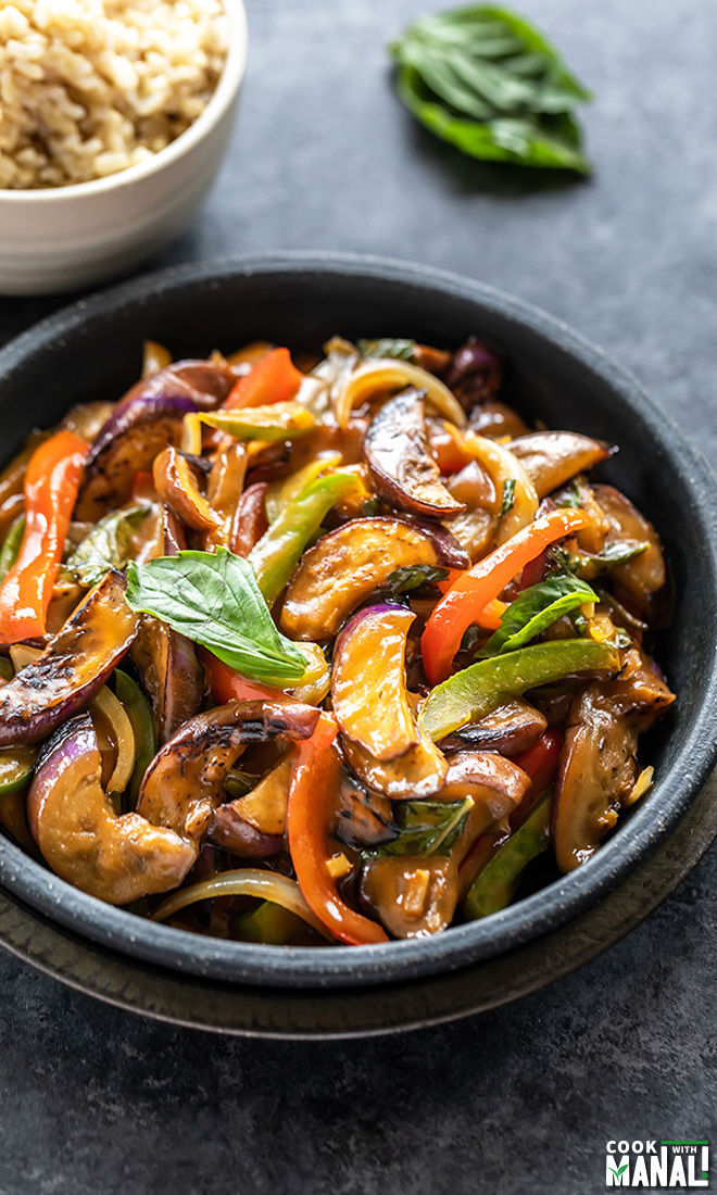 thai basil eggplant served in a black bowl and garnished with fresh basil
