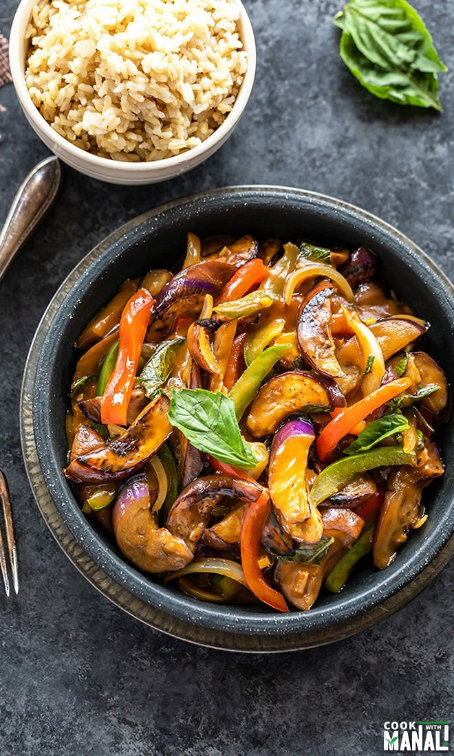thai basil eggplant served in a black bowl with a small bowl of rice in the background