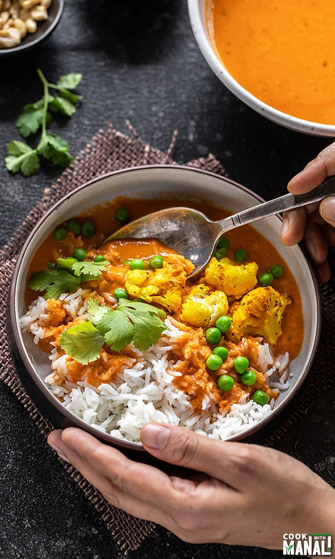 pair of hands holding a bowl of curry and rice from one side and digging into the bowl with a spoon from another hand