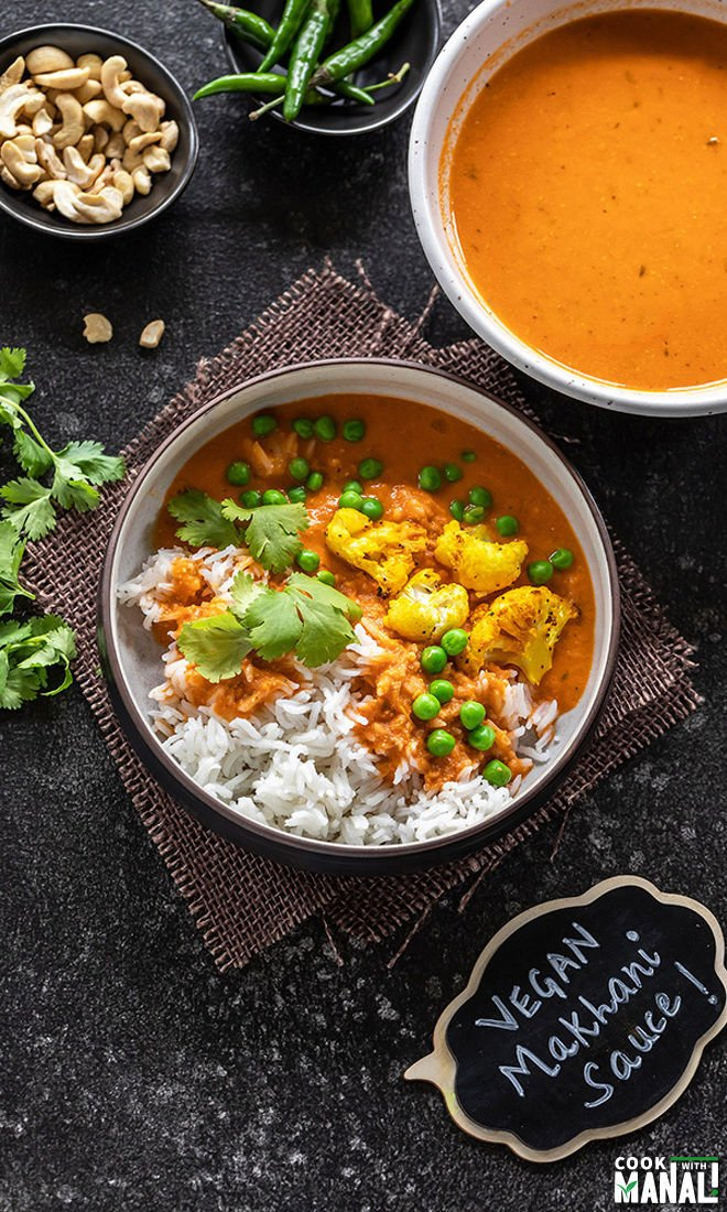 shot of vegan makhani sauce with cauliflower and green peas served over white rice and garnished with cilantro.