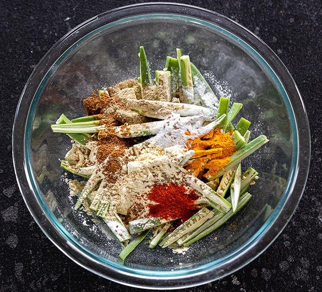 sliced okra with a bowl with spices like turmeric, garam masala, chili powder