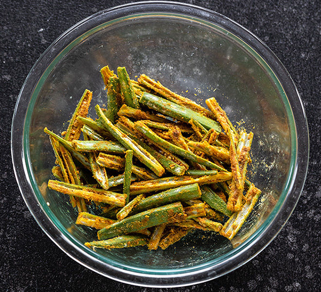 okra slices coated with Indian spices in a bowl