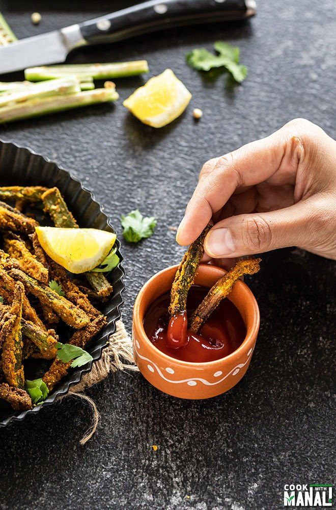 Baked Kurkuri Bhindi being dipped in a bowl of tomato ketchup