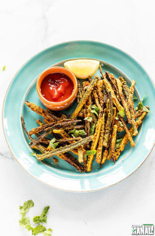 Kurkuri Bhindi arrange in a blue plate with a bowl of tomato ketchup and lemon wedge