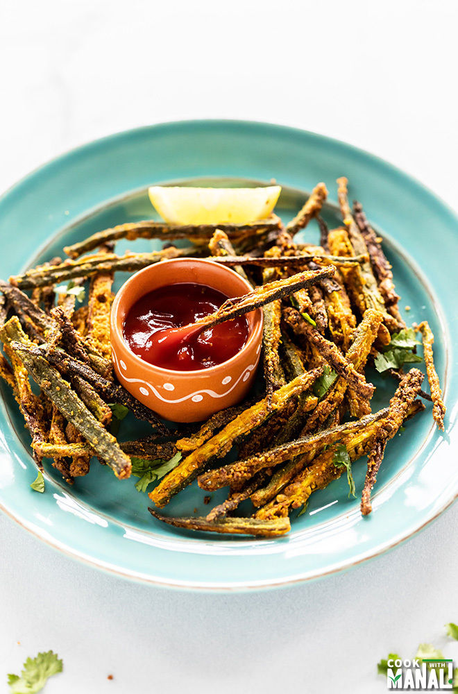 Oven Baked Kurkuri Bhindi served in a blue plate with a bowl of tomato ketchup