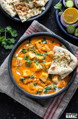 bowl of paneer butter masala served with a piece of naan and garnished with cilantro and cream