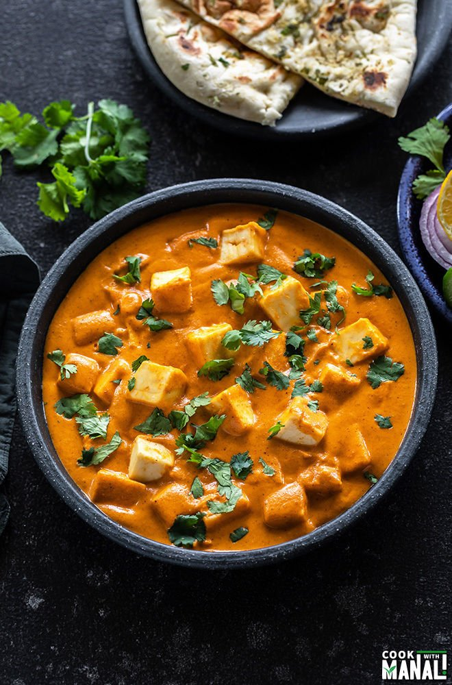bowl of paneer butter masala garnished with cilantro