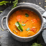 sambar served in a grey bowl garnished with curry leaves with twigs on cilantro and more curry leaves scattered all around