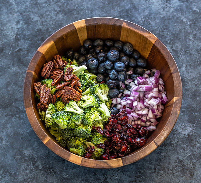 a salad bowl with chopped broccoli, onion, blueberries, pecans and dried cranberries