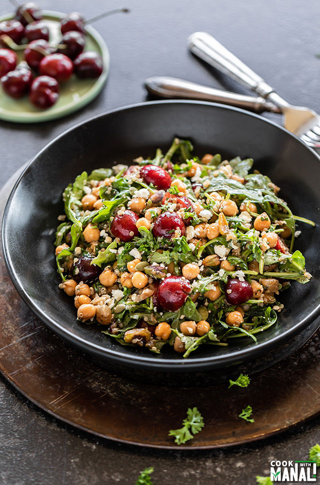 black color salad bowl filled with cherries, quinoa, arugula, chickpeas, pistachios with more cherries in the background