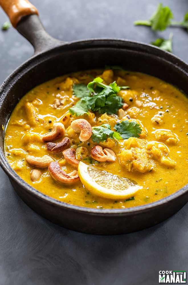 black pan filled with mango curry with cauliflower and cashews, garnished with cilantro