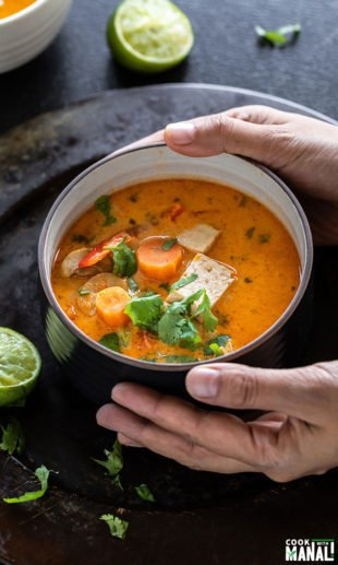 pair of hands holding a bowl of thai curry soup