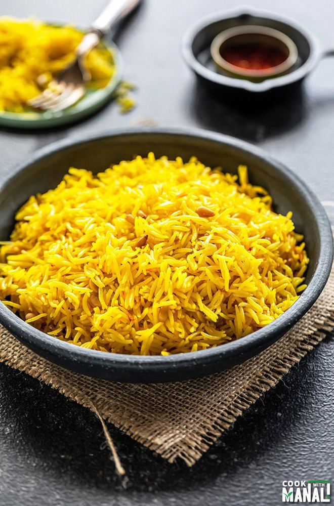 saffron rice in a black bowl with a small bowl of saffron strands in the background