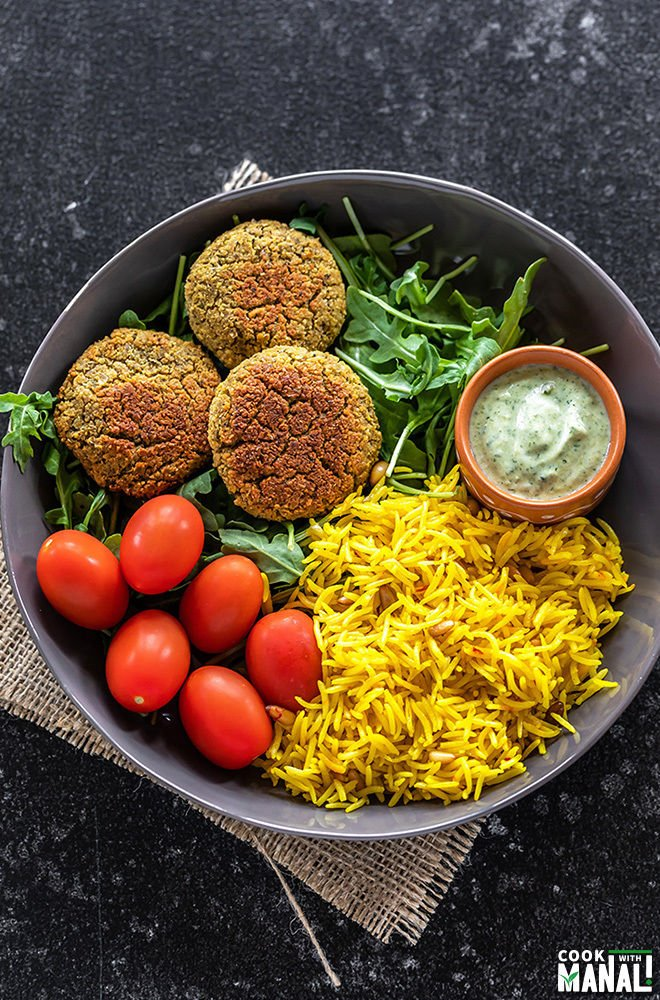 a bowl with falafel, saffron rice, greens, tomatoes and yogurt dip