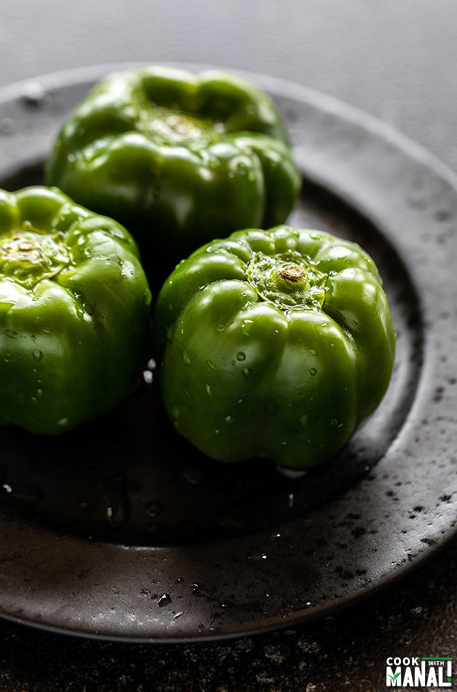 3 green bell peppers washed and arranged on a black plate