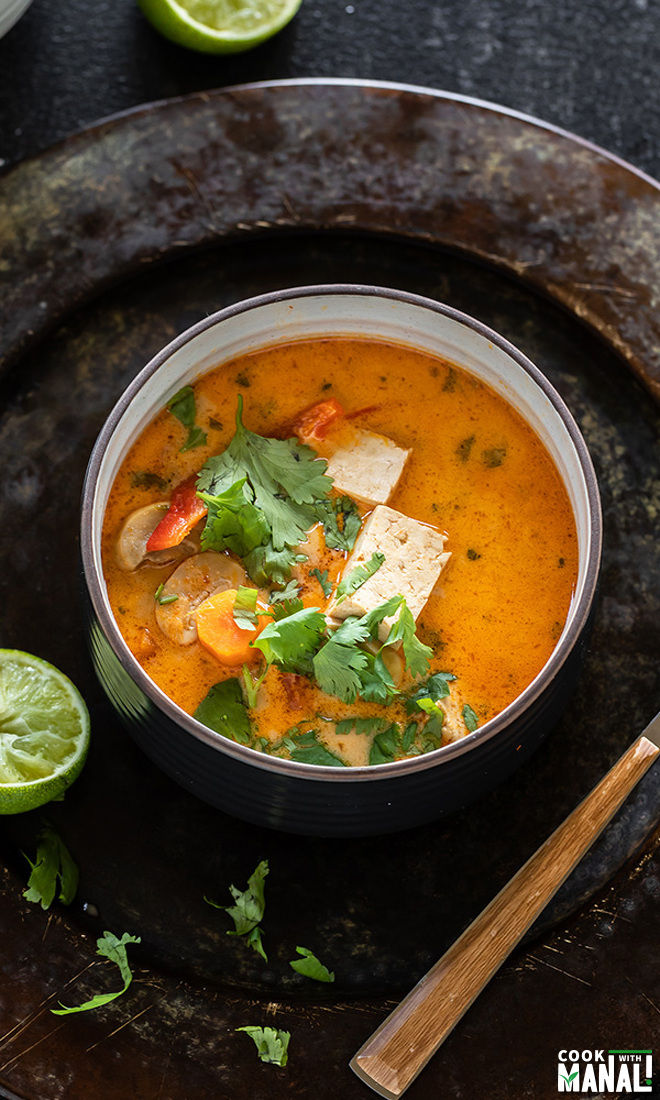 vegan thai curry soup served in a black bowl garnished with cilantro and lime wedges on the sides