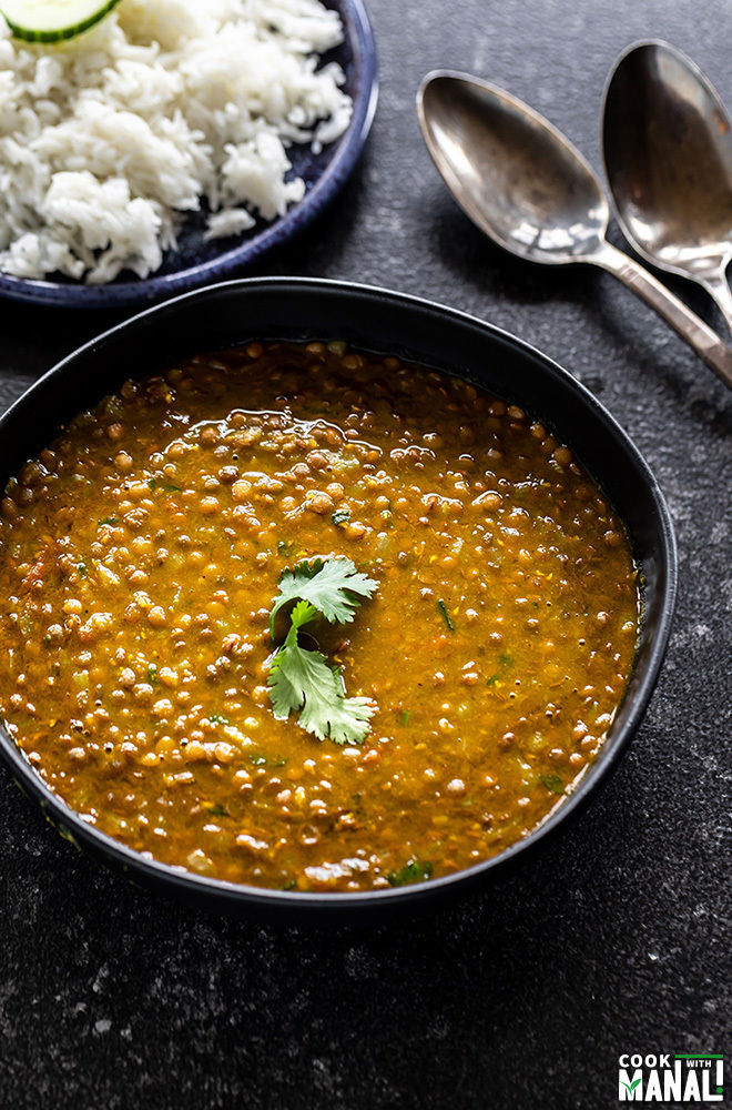 whole masoor dal served in a black bowl and garnished with cilantro