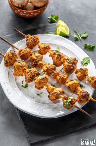 three wooden skewers of mushroom tikka arranged on a white plate and garnished with cilantro