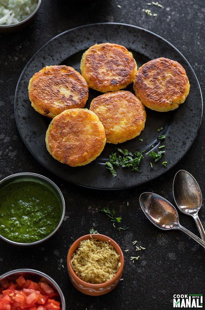 plate of 5 potato patties in a black plate surrounded by several bowls of chutney and sev