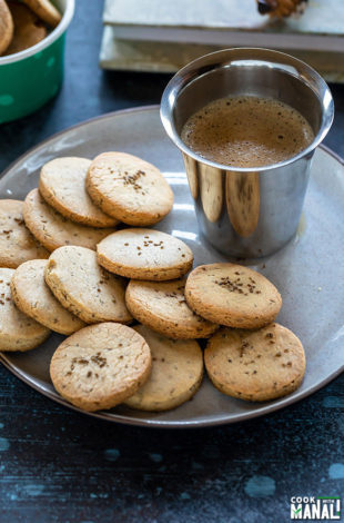 ajwain cookies in a plate with a glass of coffee