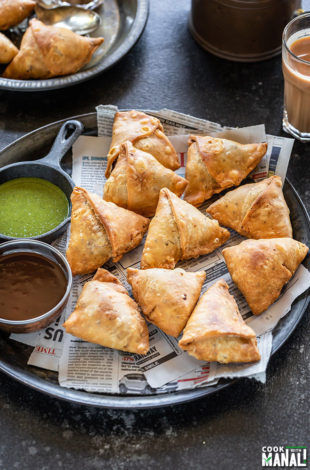 samosa served in a plate with two bowls of chutney and glass of chai on the side