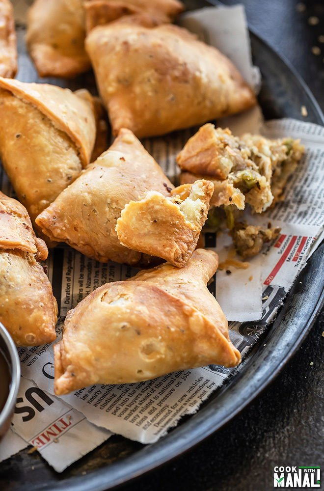 plate of samosas with one samosa broken to show the interior potato filling and the flaky crust