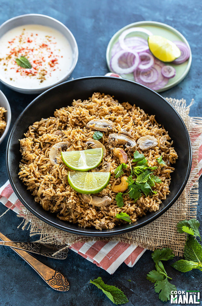 mushroom biryani served in a black bowl with bowl of yogurt and plate of sliced onions in the background