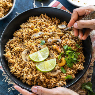 pair of hand holding a bowl of mushroom biryani with one hand digging into the bowl with a spoon