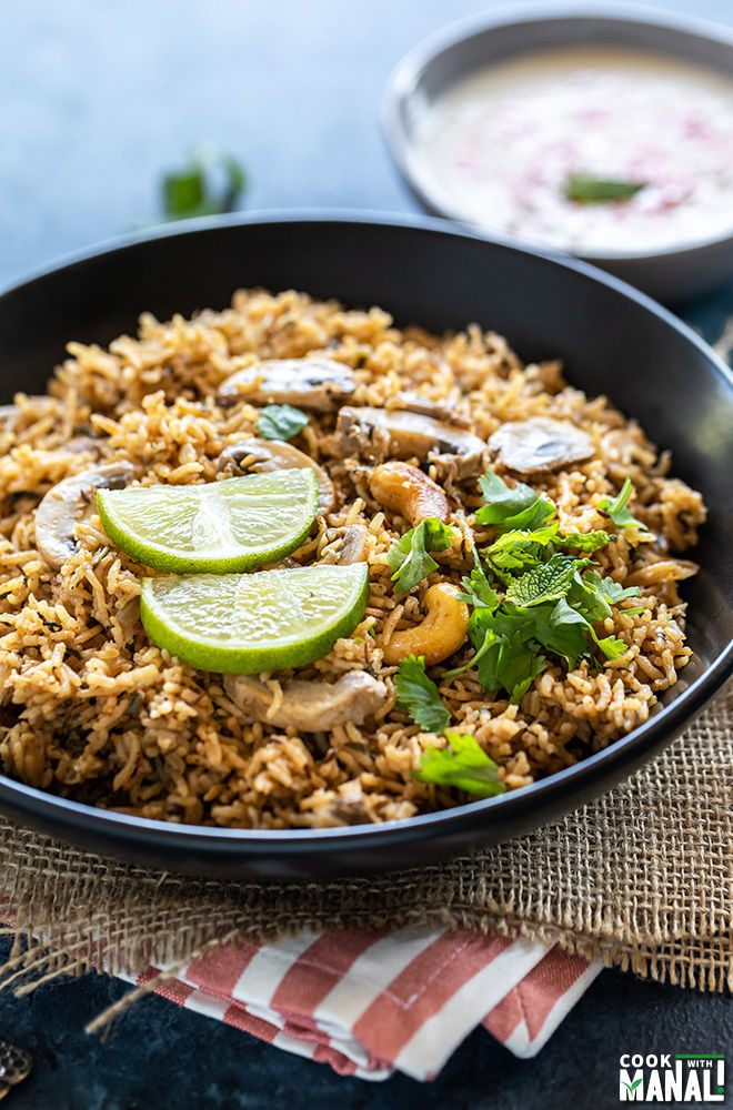 mushroom biryani served in a black bowl and garnished with lime wedges, chopped mint and cilantro