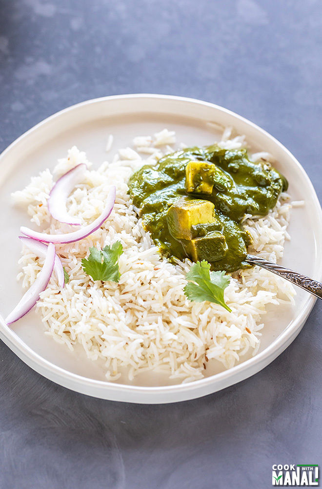 palak paneer served with basmati rice and sliced onions in a white plate