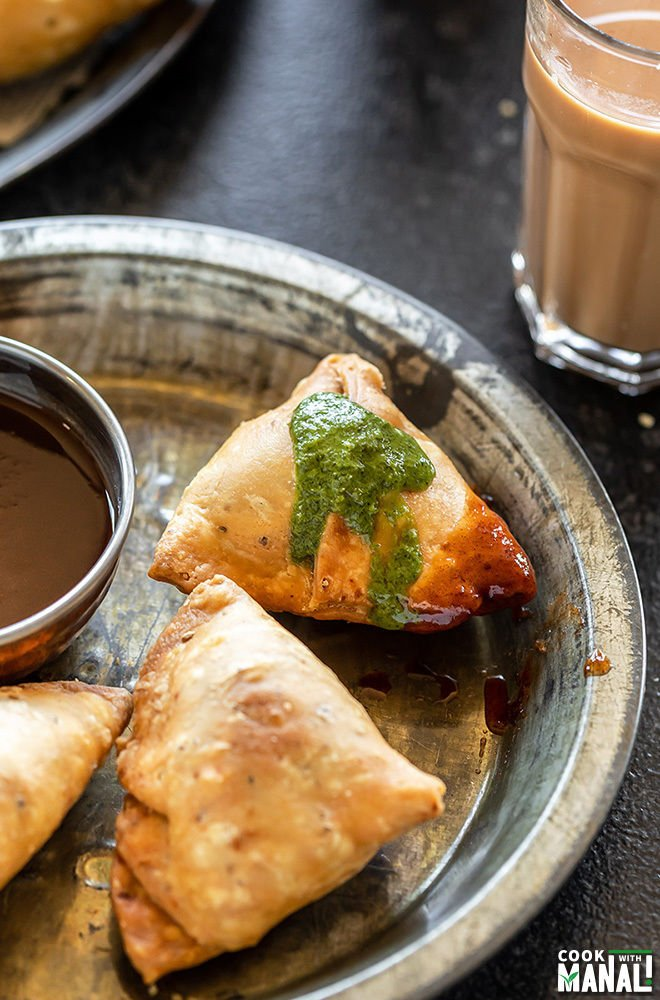 samosa topped with green chutney and sweet chutney and placed in a plate