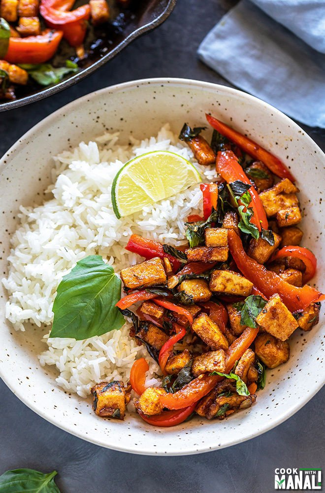 basil tofu stir fry served with jasmine rice in a white bowl garnished with lime wedge