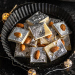 badam burfi placed in a black plate surrounded by lights and a plate of almonds in the background