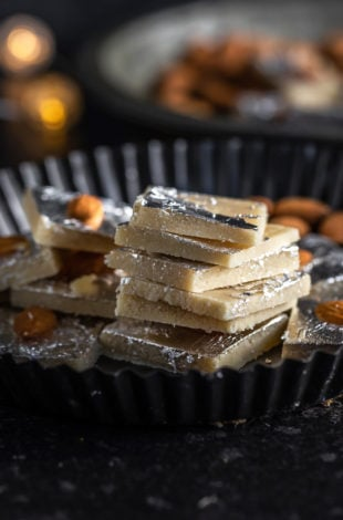 stack of badam burfi in a plate with some lights in the background