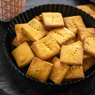 baked besan papdi in a black plate with a cup of coffee in the background