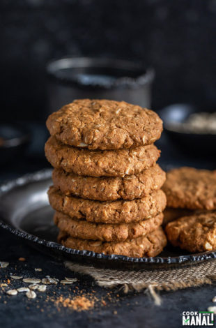 stack of oats jaggery cookies with a cup in the background