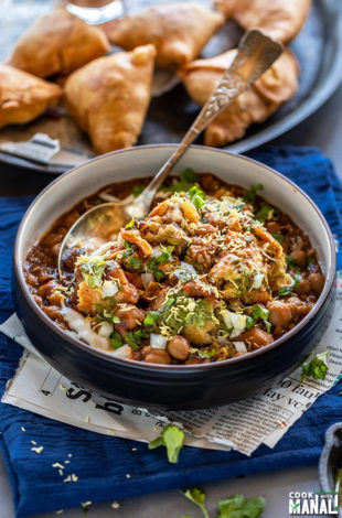 samosa chaat in a black bowl with a spoon with plate full of samosa in the background
