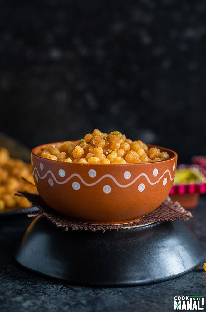 sweet boondi served in a clay bowl with diyas in the background
