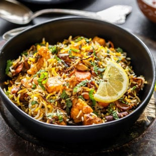 bowl of vegetable biryani garnished with lemon wedge and some spoons placed in the background along with a plate of sliced onions